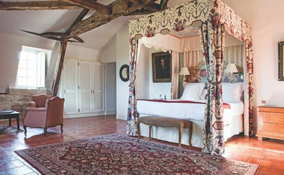Chateau des Vigiers Dordogne prestige suite bedroom with exposed wooden beams four poster bed with floral canopy