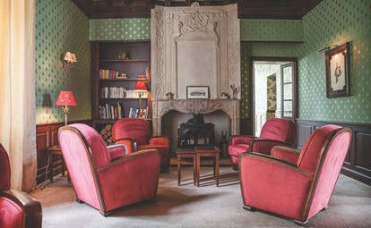 Chateau des Vigiers Dordogne lounge area with large fireplace and armchairs