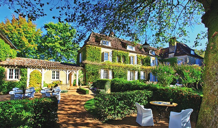 Le Vieux Logis Dordogne exterior large building covered in foliage overlooking tables and chairs