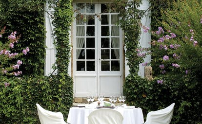 Le Vieux Logis Dordogne outdoor dining area in a garden with purple flowers