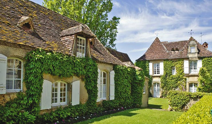 Le Vieux Logis Dordogne outdoor exterior two foliage covered buildings with white shuttered windows