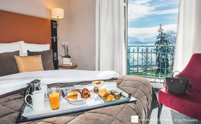 L'Imperial Palace Alps classic bedroom with a breakfast tray lake view