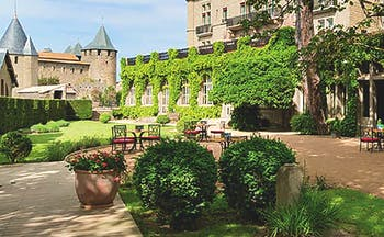 Hotel de la Cite Carcassonne Languedoc Roussillon exterior chateau and white building garden and seating area