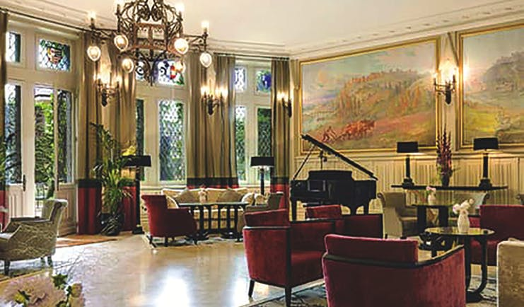 Hotel de la Cite Carcassonne Languedoc Roussillon lounge area with armchairs a grand piano and paintings