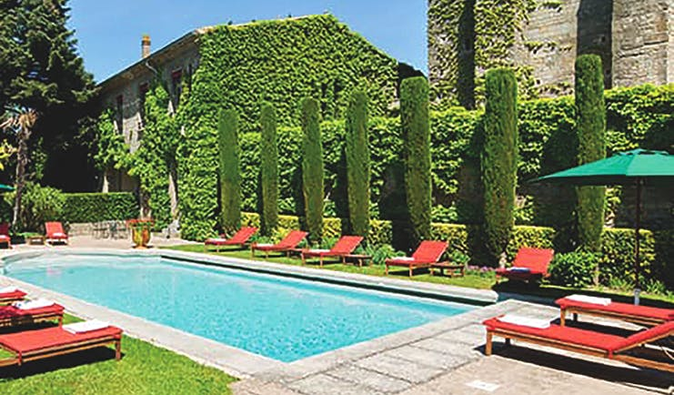 Hotel de la Cite Carcassonne Languedoc Roussillon pool with sun loungers umbrellas and topiary bushes