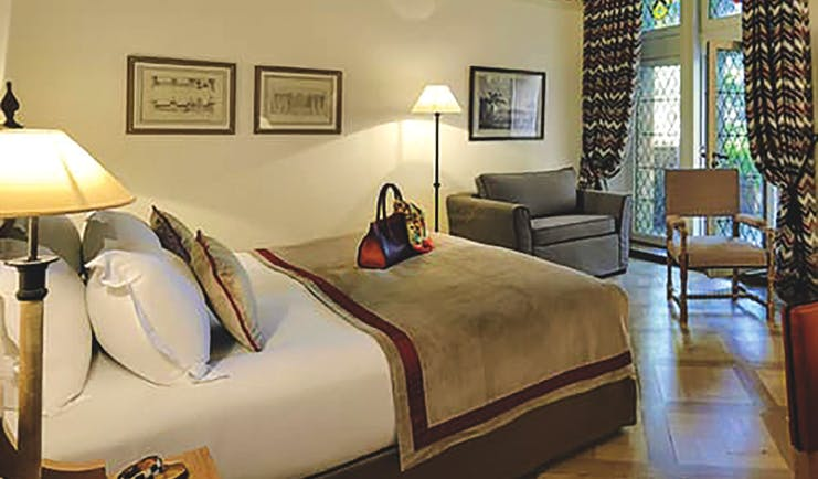 Hotel de la Cite Carcassonne Languedoc Roussillon suite bedroom with armchair chair and stained-glass window