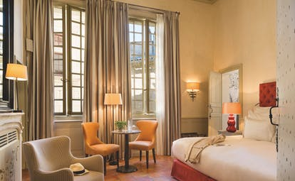 Maison d'Uzes Languedoc Roussillon junior suite bedroom with red head board white fireplace