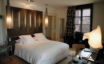 Le Domaine de Verchant Languedoc Roussillon bedroom with wooden bedhead glass desk and chair
