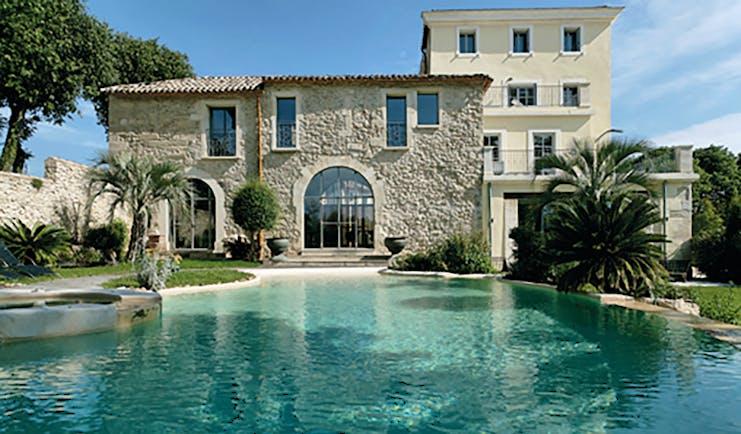 Le Domaine de Verchant Languedoc Roussillon swimming pool large stone building palm trees gardens