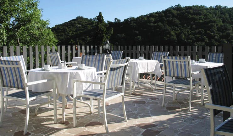 Relais des Chartreuses Languedoc Roussillon terrace area with several tables and chairs surrounded by trees