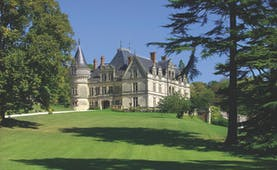 Chateau de la Bourdaisiere Loire Valley exterior large chateau with turrets and a grey roof overlooking lawn