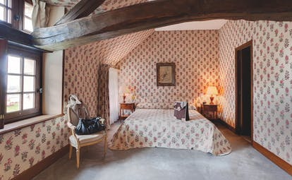 Chateau de Marcay Loire Valley bedroom with exposed wooden beams floral wallpaper and bedside tables