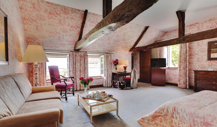Chateau de Marcay Loire Valley large bedroom exposed wooden beams sofa and coffee table