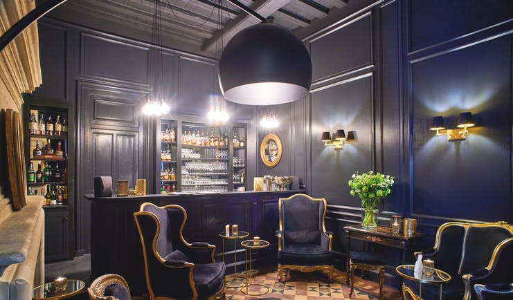 Chateau Noirieux Loire Valley bar area with dark blue walls dark blue and gold chairs and fireplace