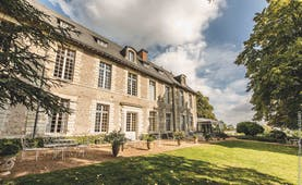 Chateau Noirieux Loire Valley exterior shot stone chateau with large windows and white metal chairs