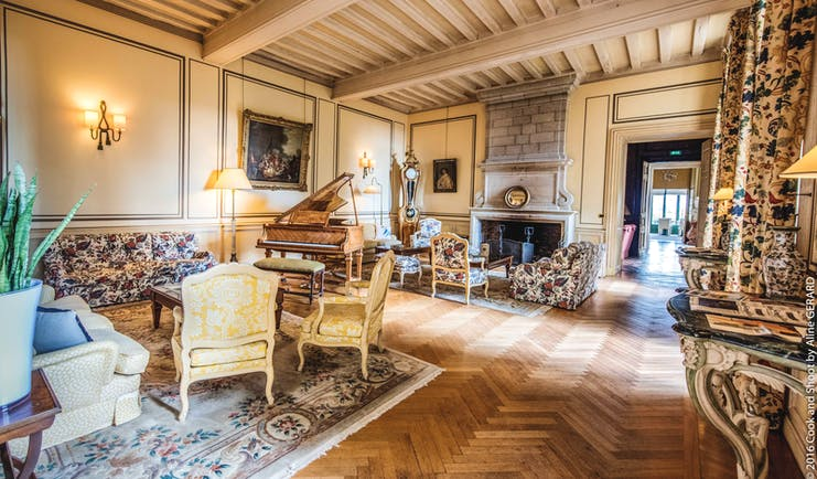 Chateau Noirieux Loire Valley salon lounge area with armchairs grand piano and large fireplace