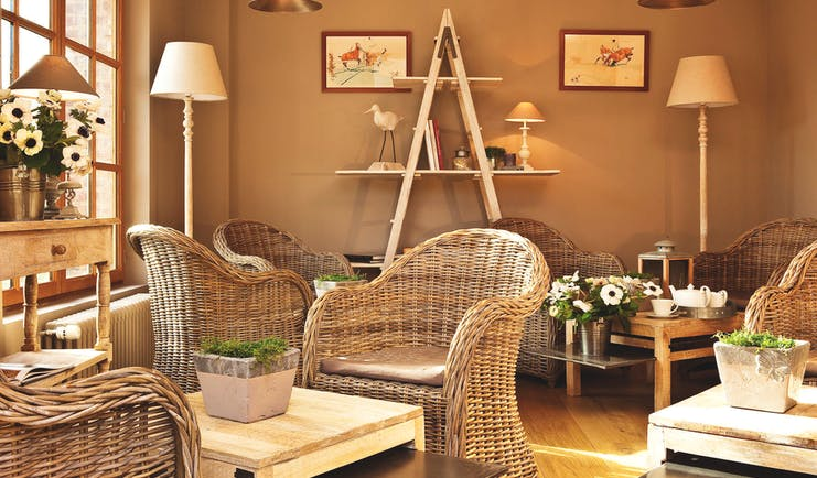 Auberge de la Source Normandy lounge area with brown wicker chairs