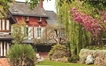 Auberge de la Source Normandy outdoor garden brick building overlooking trees with pink blossom and bushes