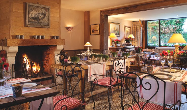 Auberge de la Source Normandy restaurant dining area with wooden tables and large fireplace