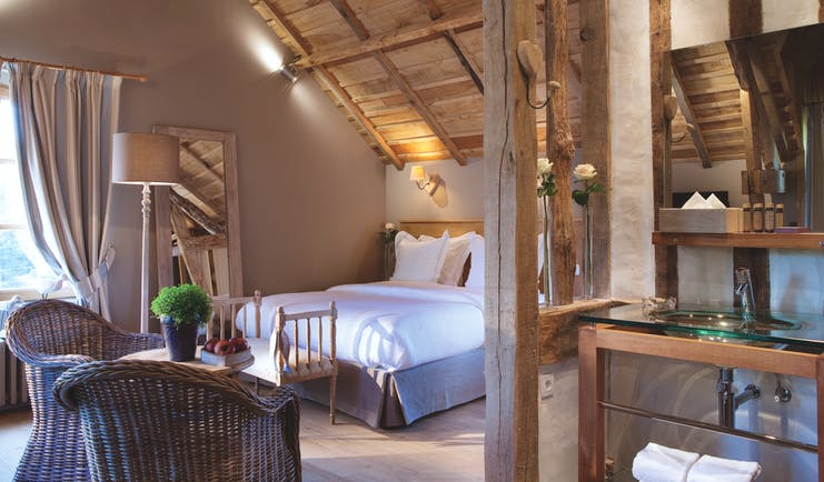 Auberge de la Source Normandy superior room with wooden roof exposed beams wicker chairs and a glass sink area
