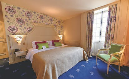 Another bedroom at the Chateau d'Audrieu with blue carpets, a large double bed, and armchair