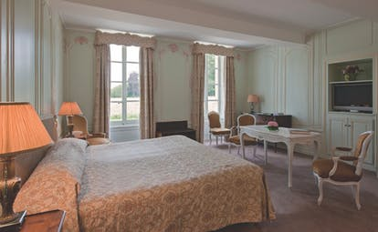 Bedroom at the Chateau d'Audrieu with a blue and gold colour scheme, large oduble bed and lamp