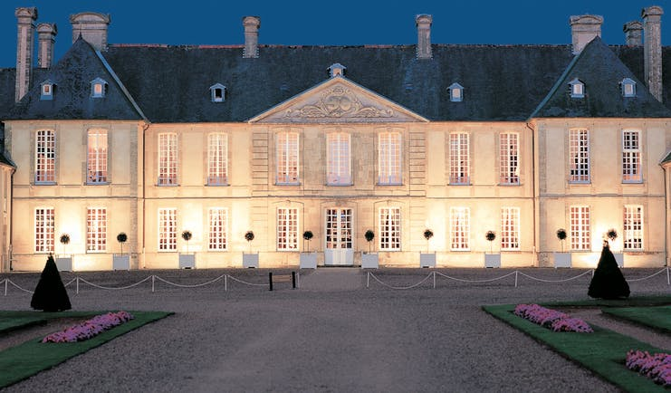 Exterior of the Chateau d'Audrieu, shows big white hotel building lit up with yellow lights