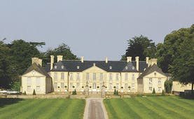Exterior of Chateau d'Audrieu with a mown lawn in front of the big white hotel building