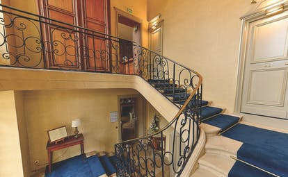 Reception with blue staircase spiraling round the corner