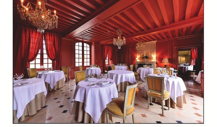 Chateau d'Audrieu dining area with red ceilings and walls and dining tables set up around the room