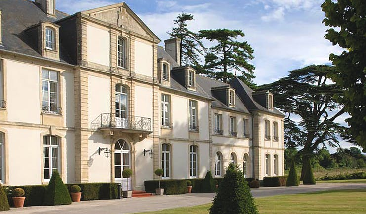 Chateau de Sully exterior, hotel building, balcony windows, lawns, trees