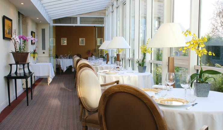 Chateau de Sully restaurant, tables and chairs, fresh modern decor, tables placed in front of window