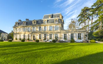 Yellow stone classical French chateau with lawns and trees Chateau la Cheneviere Normandy