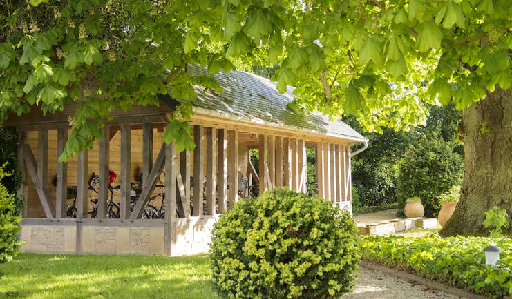 Outdoor stable area with bushes and trees with large wooden stable area with bikes inside