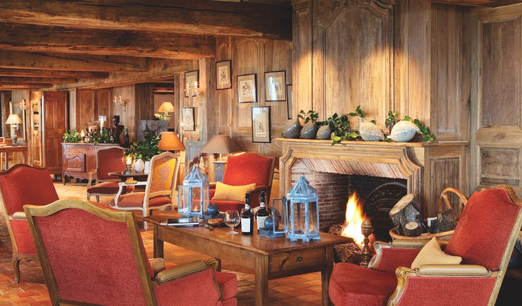 La Ferme Saint Simeon Normandy lounge area with wooden walls exposed beam and a fireplace
