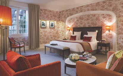 Bedroom at the Hotel Barriere with double bed, arm chairs and flower arrangements