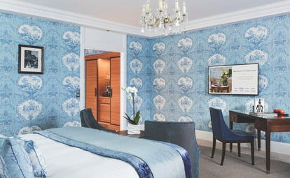Double room at the Hotel Barriere with blue colour scheme, a double bed, large flat screen television and walk in wardrobe