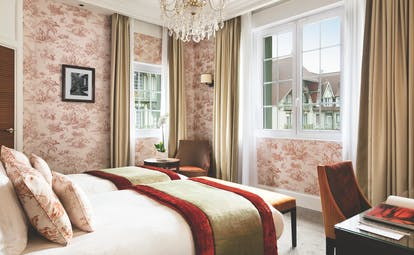 Twin room with two single beds, pink, red and beige colour scheme and two large windows with a glass chandelier hanging from the ceiling