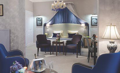 Hotel Royal Barriere prestige suite, elegant decor, blue velvet armchairs, seperate seating area, canopied bed