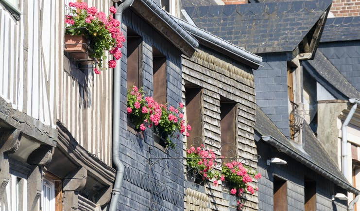 Rustic grey and brown houses with pink flowers in windowboxes in Honfleur