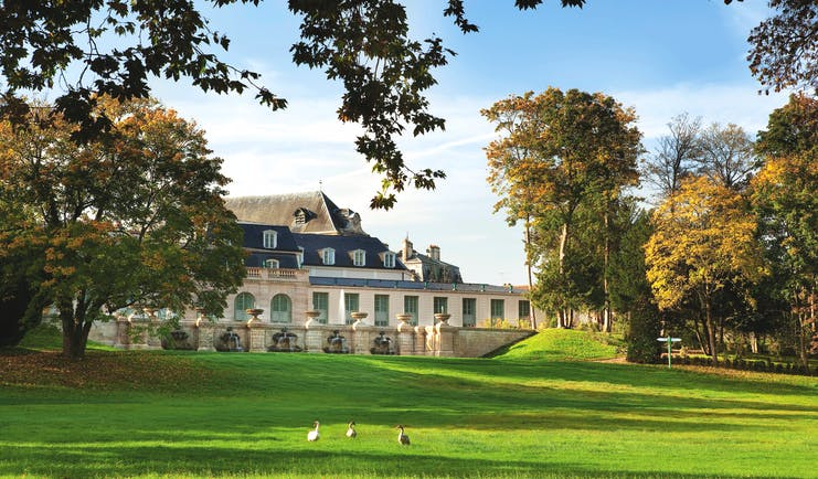 Auberge du Jeu de Paume Paris exterior lawn large white building with grey roof overlooking a lawn and trees