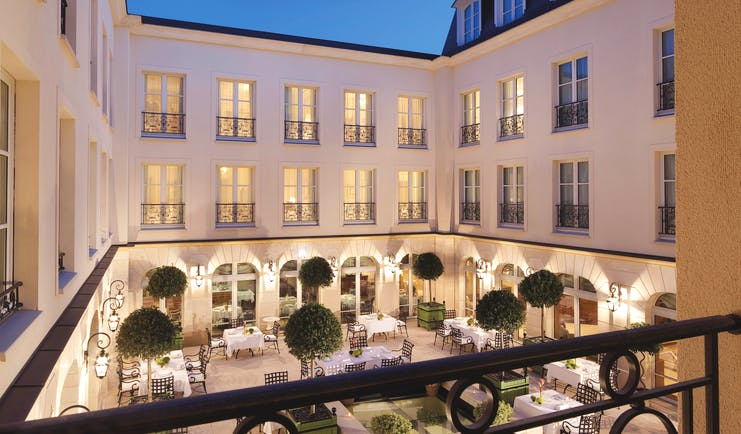 Auberge du Jeu de Paume Paris exterior courtyard with several tables and chairs overlooked by a white building