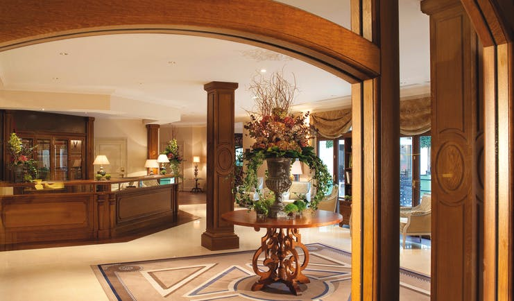 Auberge du Jeu de Paume Paris lobby with wooden beams table with large floral arrangement chandelier