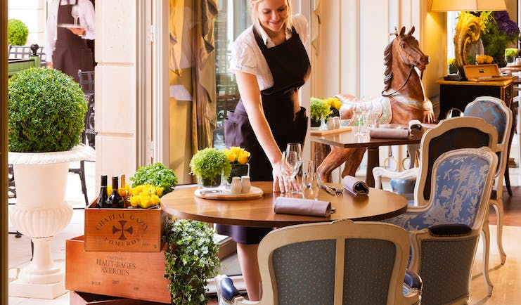 Auberge du Jeu de Paume Paris restaurant dining waitress setting table in front of a carved wooden rocking horse