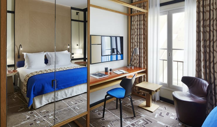 Hotel Bel Ami Paris bedroom with blue covers on bed and large mirror