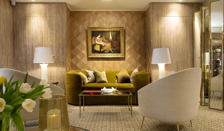 Lobby area with seating areas set out, paintings on the wall and lamp shades
