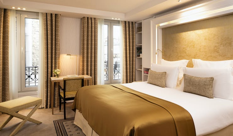 Privilege suite with large double bed and gold colour scheme