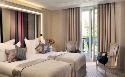 Twin room with two twin beds, arm chairs and balcony