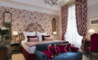Deluxe room with floral patterned wallpaper, double bed, sofa and draping curtains
