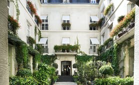 Relais Christine Paris courtyard with plants and exterior with white shutters at windows